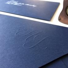 Monograma embosado en sobre de cartulina azul marina.