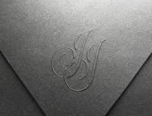 Monograma embosado en sobre de cartulina metálica matte.
