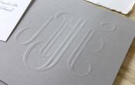 Monograma embosado en solapa de sobre de cartulina gris.